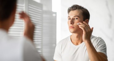 Confident man in white shirt in mirror applying moisturizer after face mask